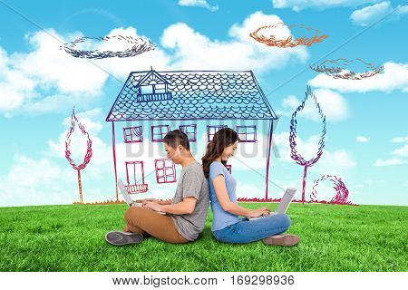 Happy young couple using laptop while sitting back to back against blue sky over green field