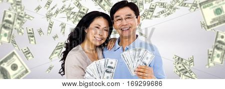 Smiling couple with two fans of cash against dollars falling