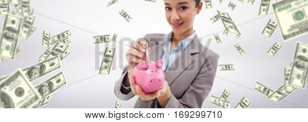 Portrait of a businesswoman putting a bank note in a piggy bank against dollars falling