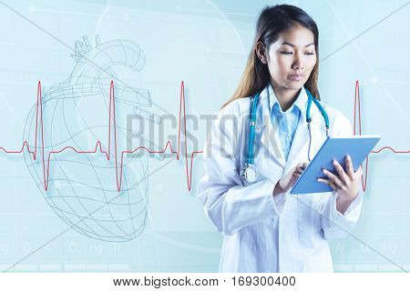 Asian doctor using tablet against hearth illustration behind a heartbeat line