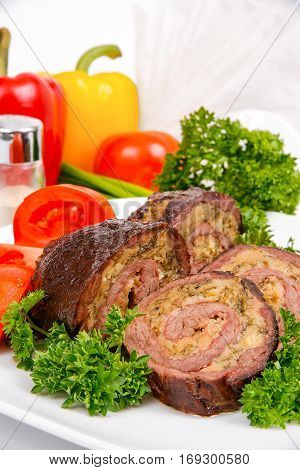 Meatloaf with tomato and herbs on a white plate