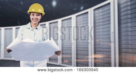 Architect reading a plan with yellow helmet against composite image of server towers