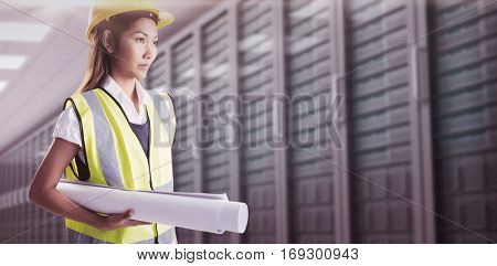 Architect woman with yellow helmet and plans against server room with towers