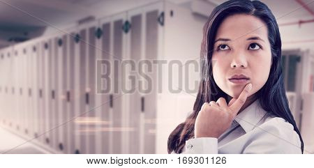 Thoughtful businesswoman with finger on chin against data center