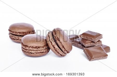 Delicious brown colored macaroons, isolated on white background. Studio isolated chocolate macaroon candy with chocolate pieces.