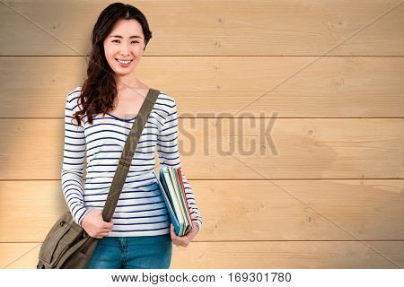 Cheerful woman with shoulder bag and files against bleached wooden planks background