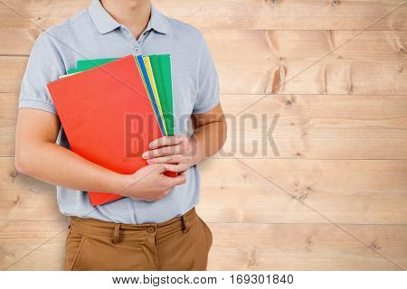Mid section of man holding files against bleached wooden planks background
