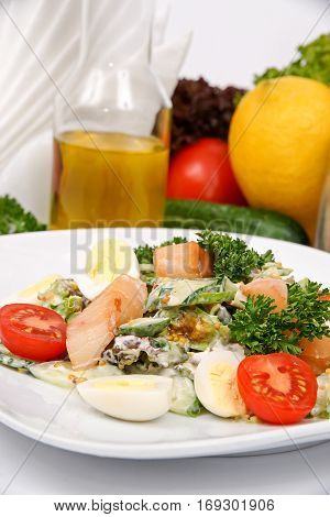 Catfish salad with mustard sauce with herbs on a white plate