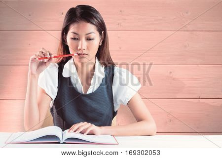 Thoughtful businesswoman reading against bleached wooden planks background