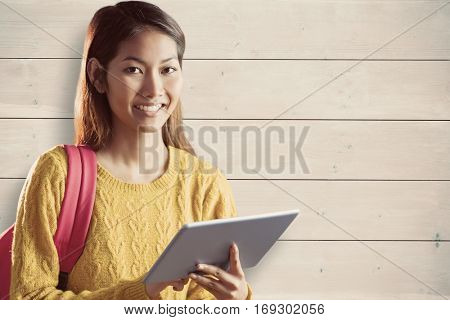 Smiling asian female student using tablet against bleached wooden planks background