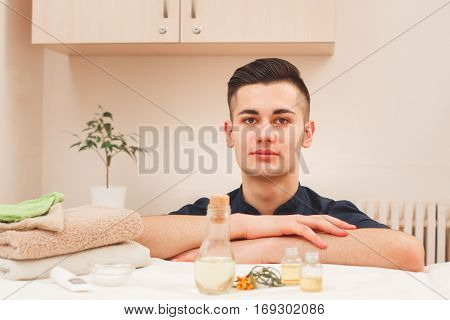 Portrait of handsome male masseur in black apron. Young smiling male professional massagist posing at workplace near aroma therapy set, looking at camera