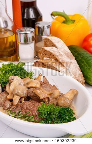 Fricassee of veal brisket with mushrooms on a white plate with fresh herbs