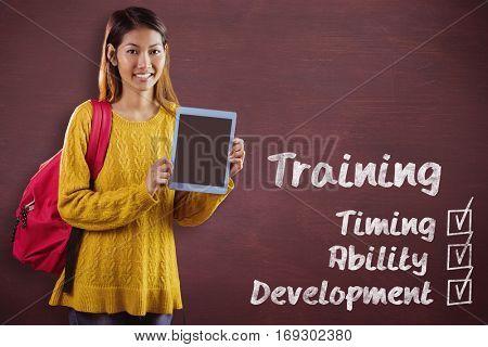 Smiling asian female student showing tablet against desk