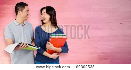 Couple smiling at each other while holding books against bleached wooden planks background