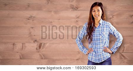 Smiling asian woman with hands on hips against bleached wooden planks background