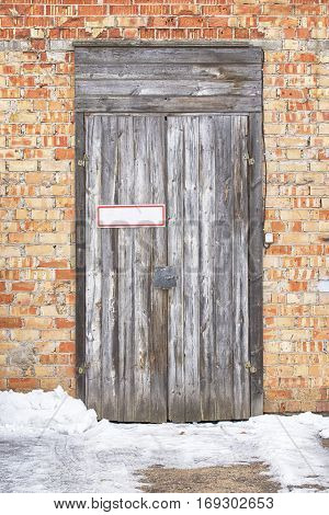 wooden plank door with metal plate for text, brick wall background