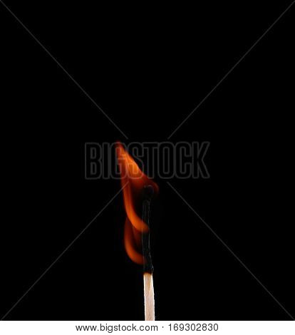 Ignition of a match with smoke on dark background. Hand holding burning match stick