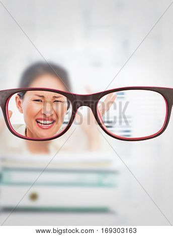 Glasses against angry businesswoman shouting with stack of folders at desk