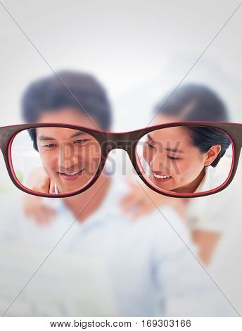 Glasses against couple reading a newspaper together