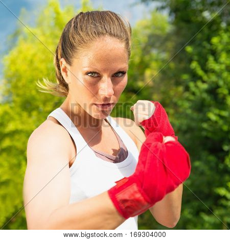 Portrait of beautiful female fighter, toned image, outdoors