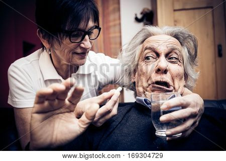 a senior man refusing to take the pills his nurse is trying to give him