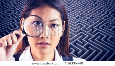 Businesswoman looking through magnifying glass against difficult maze puzzle