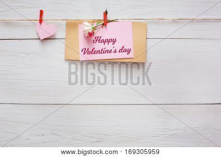 Valentine background with heart on clothespins and paper card with rose flower on rustic wood planks. Happy lovers day mockup, copy space