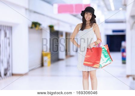 Pretty woman with shopping bags against interior of modern shopping mall