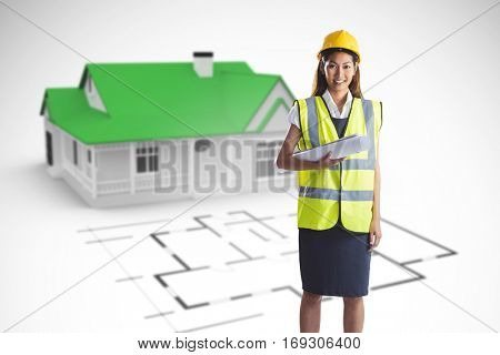 Architect woman with yellow helmet and plans against blue house behind an architectural plan
