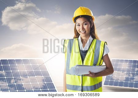 Architect woman with yellow helmet and plans against solar panels on floorboards in the sky
