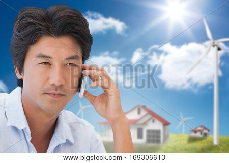 Serious man on a phone call against houses in a turbine field