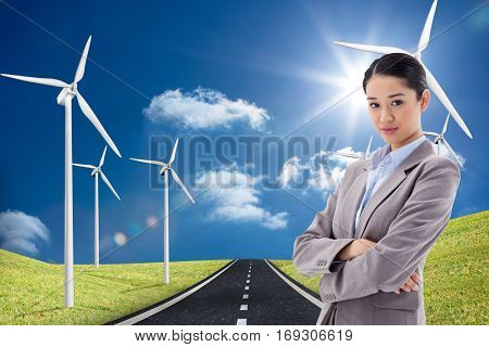 Portrait of a gorgeous businesswoman posing with the arms crossed against road leading out to the horizon with wind turbines either side