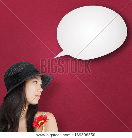 Cheerful woman with flower looking away wearing a hat against red vignette