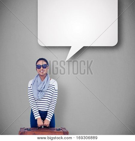 Asian woman with luggage looking at the camera against grey vignette