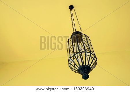 Vintage Lamp Hanging From The Ceiling With Modern Yellow Interior Room.