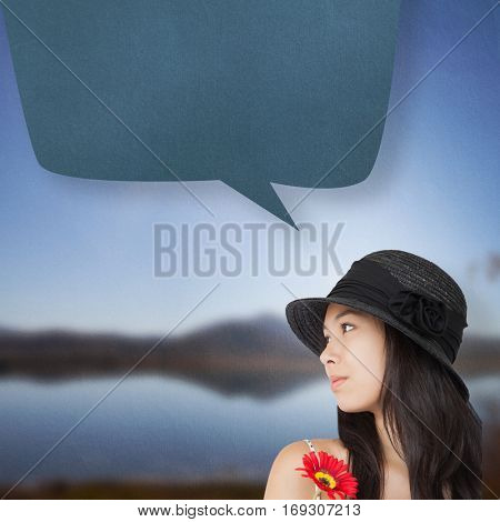 Cheerful woman with flower looking away wearing a hat against lake