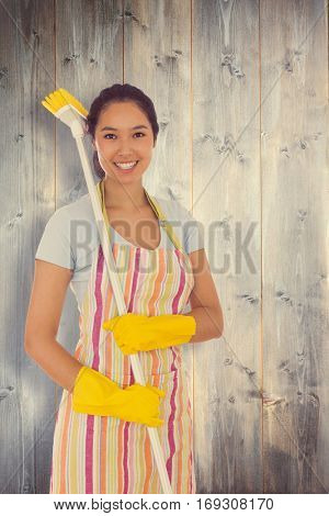Smiling woman with a broom on her shoulder against bleached wooden planks background