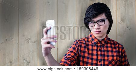 Cinfident hipster taking a selfie against wooden planks