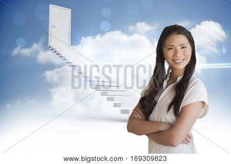 Casual businesswoman looking at camera with arms crossed against steps leading to closed door in the sky