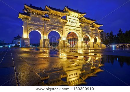 Asia culture - night view of Liberty Square (Archway of Chiang Kai Shek Memorial Hall) with reflection in raining day Taipei Taiwan. the Chinese text on the archway : Liberty Square