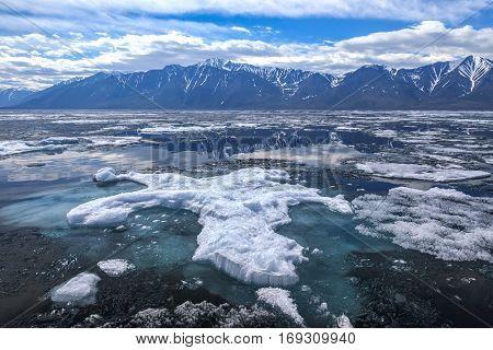 Big ice floe with blue underwater foundation, spring landscape