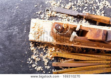 old tools: wooden planer and chisel in a carpentry workshop on dark background top view with copy space