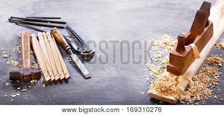old tools: wooden planer hammer chisel in a carpentry workshop on dark background banner