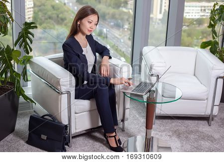 Young Asian Business Woman In Suit Working At A Laptop