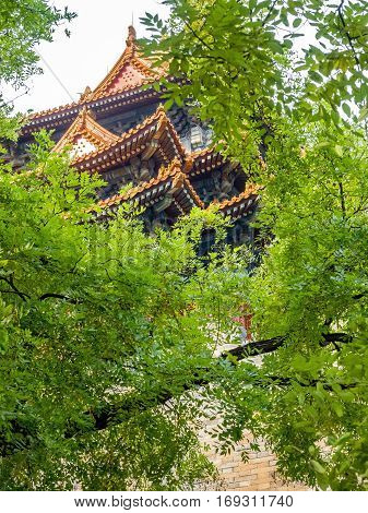Beijing, China - Oct 30, 2016: Lush green leaves veiling the Jiaolou Tower. View from outside the wall of the Forbidden City (Gu Gong, Palace Museum) on Donghuamen Road.