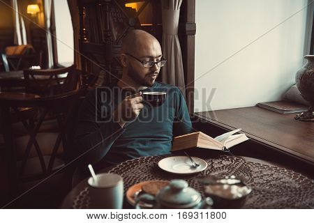 a young man with glasses beard sitting in cafe and reading a book