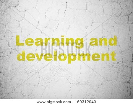 Learning concept: Yellow Learning And Development on textured concrete wall background