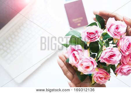 Woman hand holding bouquet of pink rose with laptop and passport background Valentines day concept