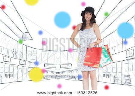 Pretty woman with shopping bags against dot pattern