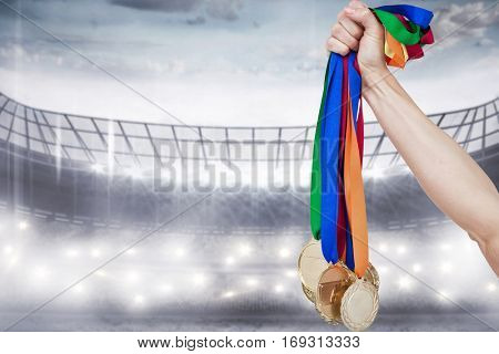Close up of a hand holding medals against sports arena
